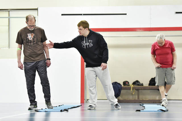 John Banks, left to right, gets instruction on an exercise technique from YMCA wellness instructor and youth sports coordinator Matthew Linsey, both of Sidney, during a Parkinson's disease exercise class Thursday, April 25. Also stepping in and out of the ground ladder is Dave Baker, of Piqua. The Parkinson's disease exercise class is called Delay of the Disease. It is designed to help people fighting Parkinson's disease continue to function as well as possible in daily life.