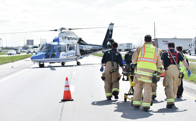 Sidney firefighters and CareFlight workers push a person towards CareFlight, which landed on the northbound lanes of I-75 next to a major crash that happened in the southbound lanes of I-75 near mile marker 93 around 3 p.m. Sunday, April 28. Two semitrailers sustained major damage in the crash. One of the semitrailers was carrying cheddar and onion baguettes which spilled out onto the road.