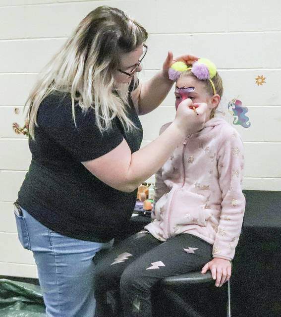 Anne Fahncke, of Wapakoneta, member of the Face Paint Crew paints the face of Avah Roediger, 9, of Sidney, daughter of Jakki, and Clay Roediger during the YMCA Healthy Kids Day Saturday, April 27.