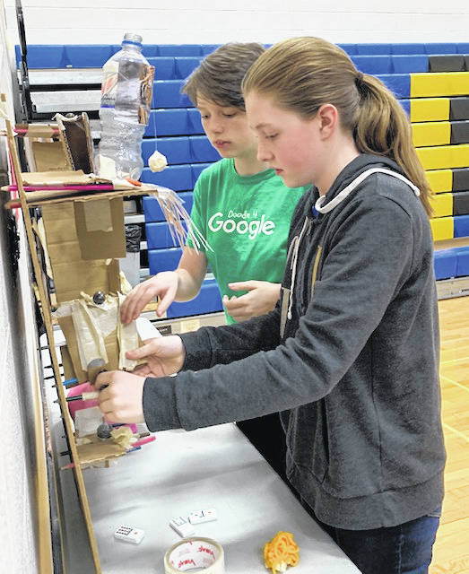 Sixth grade students Abigail Sullenberger, left, daughter of Eric and Rachel Sullenberger, and Lilli McClenen, daughter of Jessica and Chad McClenen, work to prepare their Rube Goldberg machine to demonstrate during Russia's STEM night on Tuesday, April 16. Sullenberger and McClenen built the machine, which is designed to perform the simple task of inserting a penny into a piggy bank in an indirect and over-complicated fashion, along with classmates Grace Monnin and Emma Caldwell.