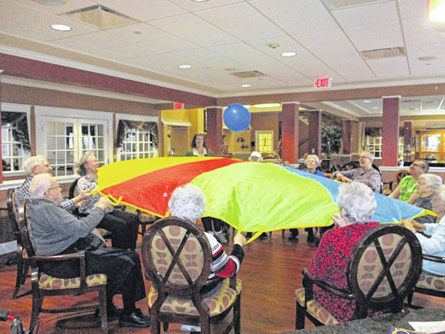 Residents of Elmwood Assisted Living in New Bremen have fun with a parachute and a ball, recently.