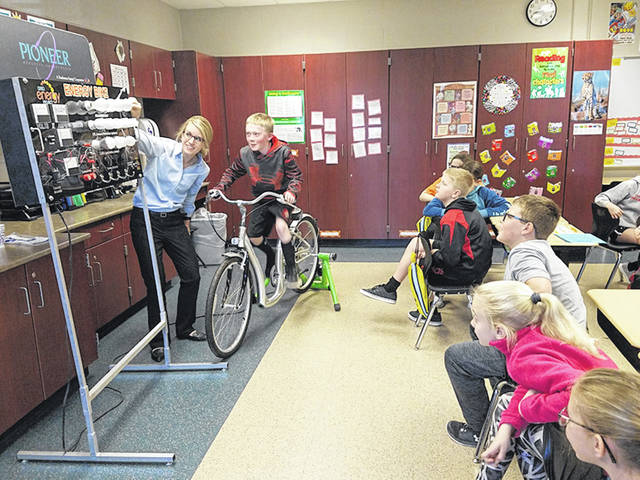 Jodi Borger, left, of Pioneer Electric, explains to Fort Loramie Local Schools fourth-graders how energy created by their fellow student, Jackson Frilling, son of Jessica and Adam Frilling, of Fort Loramie, as he pedals an energy bike lights up bulbs.