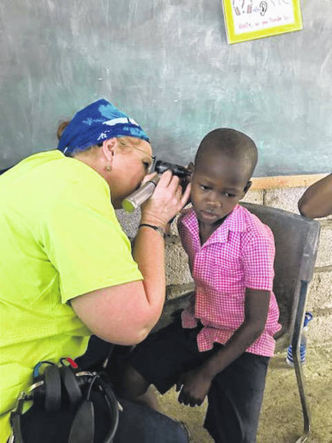 Vanessa Lee, of Wapakoneta, owner of Sidney Audiology, checks the ear of a Haitian child during a recent mission trip.