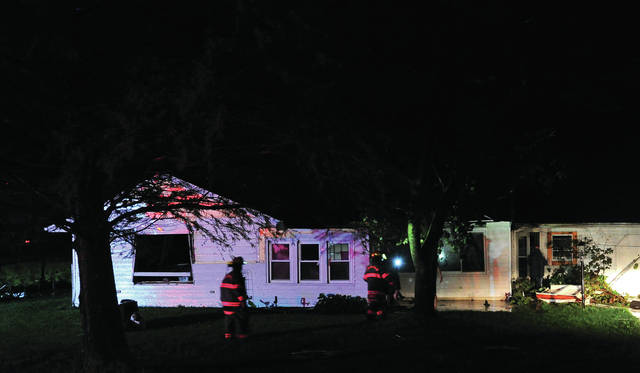 Firefighters check a home on State Route 48 north of West Milton that sustained storm damage on Monday. See more storm coverage on Page 15.