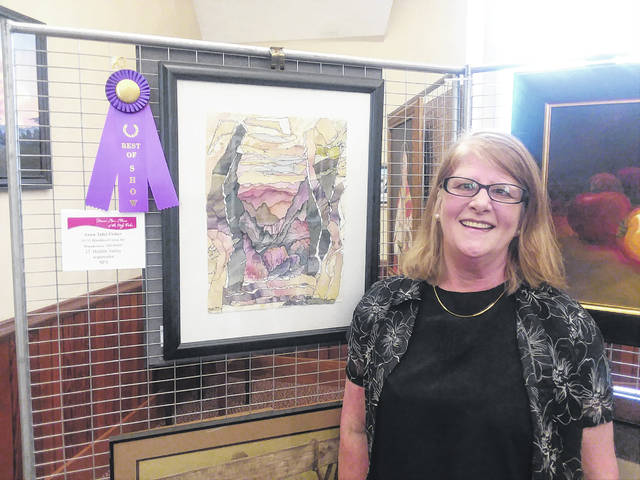 The 2018 Art Show Winner, Anna Talei Fisher, is shown with her winning artwork.