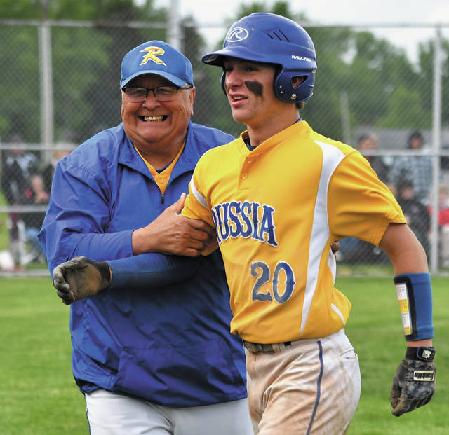 Russia assistant coach Denny Monnin, left, congratulates Aiden Shappie after Shappie scored a run in the 10th inning of a Division IV district semifinal on Monday in Sidney. Shappie's run was the only of the game and lifted the Raiders to an upset win over Fort Loramie.