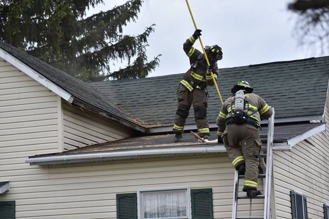 Firefighters punch holes into the roof of a house at 603 College St. in Jackson Center after a garage fire spread into the roof of the house Sunday, May 19.