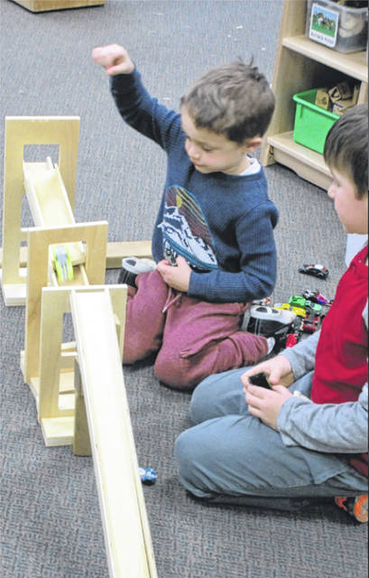 Calvin, left, and Caleb experiment with ramps and gravity in the block center of the Edison State Community College Child Development Center.
