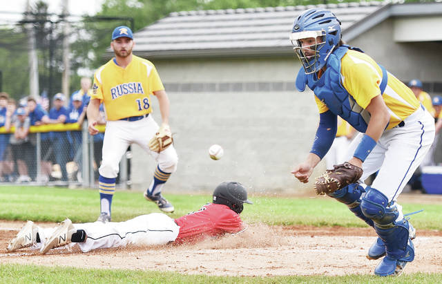 Russia's Will Sherman works to get a throw to under control as Newton's Ryan Mollette slides into home plate during a Division IV district final on Wednesday in Versailles.