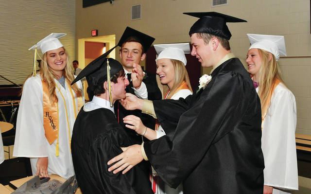 Botkins seniors help their friend with his graduation cap. Pictured are, left tor right, Grace Homan, Nick Frischio, Logan Johnson, Lindsey Okuley, Evan Aufderhaar and Adriana Jutte. Their graduation was held Sunday, May 19.