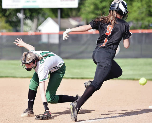 Anna's Nylah Crosson has a throw go past as Versailles' Abby Stammen reaches first base during a Division III sectional final on Wednesday in Versailles.