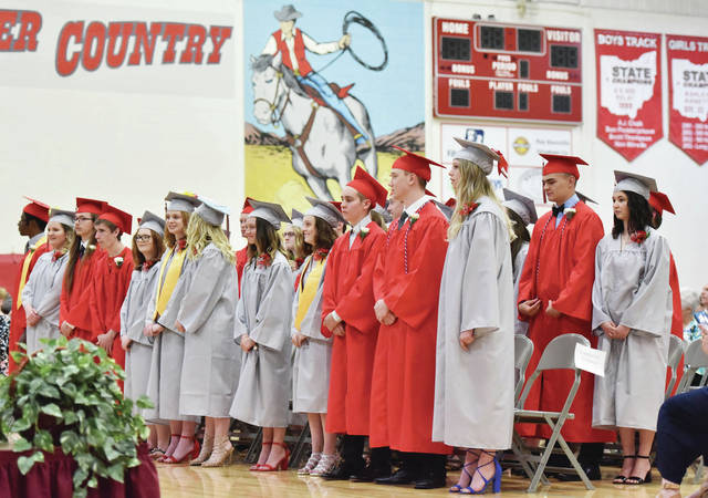 New Knoxville seniors stand by their seats at the start of the New Knoxville High School graduation ceremony Sunday, May 26.