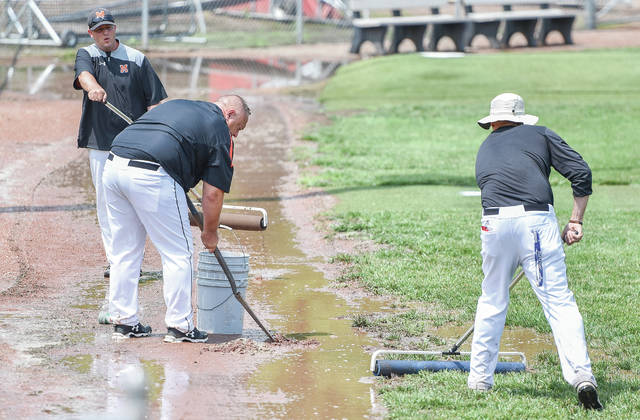 Minster coach Mike Wiss, front left, and assistant coaches try to clean up water that pooled in the warning track along the left-field line at Carleton Davidson Stadium in Springfield on Friday. Minster's regional semifinal against Mechanicsburg and Russia's regional semifinal against Cincinnati Christian scheduled for Friday were initially pushed back to 4 and 7 p.m., then moved to 6 and 9 after afternoon rain in Springfield. After attempts to dry several flooded areas (including in left field) and an hours-long conversation between stadium and school officials, both games were postponed to Saturday. The games have also been moved to Coldwater's Veterans Field. Minster's game is scheduled to start a noon on Saturday with Russia's to follow at 3 p.m.