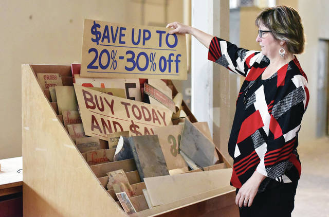 Cindy Helman, of Sidney, shows some of the old signs she found after buying the Piper building.