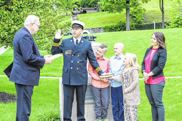 Dallas Davis receives the oath of office from Sidney Mayor Mike Barhorst Monday afternoon as he becomes the city's new assistant fire chief. Holding the Bible during the ceremony is Davis' children, Dalton, 11, Braxton, 9, and Brenna, 6, as his wife, Bridget, looks on.