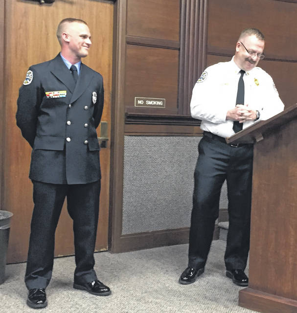 Sidney Firefighter Jeffrey Simon, left, is introduced as Sidney Fire Department's 2018 Firefighter of the Year Award by Fire Chief Brad Jones during Monday evening's Sidney City Council meeting.