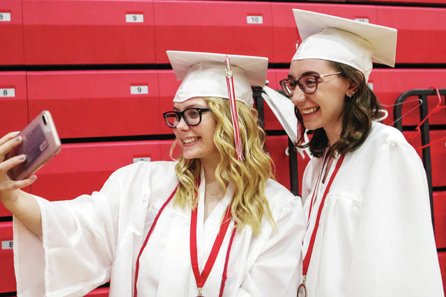 Houston High School seniors Kiaria Burkett, left, 18, daughter of Shawn and Teah Burkett, takes a selfie with Lena Stangel, 18, daughter of Jason and Karen Stangel, during the Houston High School graduation Saturday, May 19.