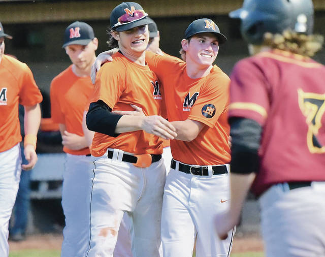 Minster's Jack Olberding, left, and Dan Gottschalk hug after defeating New Bremen in a Division IV district final on Friday in Coldwater. Olberding was 3 for 4 at the plate with 3 RBIs.