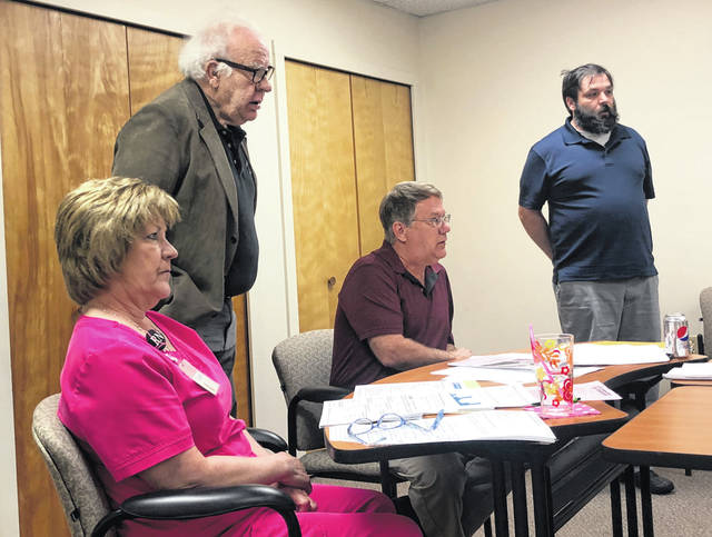 Minster Shoe Inn owners Fred Meyer and John Hobbler, both standing, discuss the violations against the restuarant during Tuesday's Auglaize County Board of Health meeting. Listening to the pair are Becky Egbert, assistant director of Nursing, and Curt Anderson, director of Environmental Health.