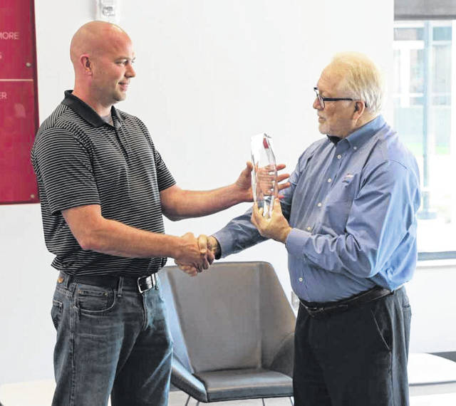 Ron Kaufman, facilities superintendent for Ohio State Lima and Rhodes State College, receives the Energy Efficiency Champion Award from Gary Hendrickson, Continuous Energy Improvement coach from AEP Ohio.