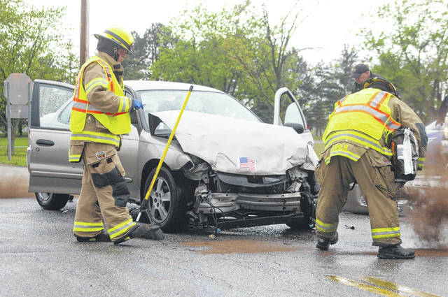 Firefighters from the Sidney Fire Department apply absorbent to the road as they clean up a two-vehicle crash Friday morning, May 3, near the intersection of Mason Road and County Road 25A outside of Sidney. According to the Shelby County Sheriff's Office, an SUV was traveling eastbound on Mason Road when the driver failed to stop for a car that was traveling northbound on County Road 25A, causing a collision. One passenger from the Chevrolet Cavalier was transported to the hospital for minor injuries.