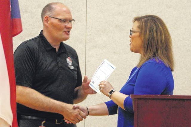 Fort Loramie Elementary Principal Scott Rodeheffer (left) accepts a certificate from Ohio Association of Elementary School Administrators Zone 3 Director Cathryn Petticrew-Rice (right) during an awards ceremony on Thursday afternoon at the school. Fort Loramie was one of seven elementary and middle schools in the state to earn the honor.