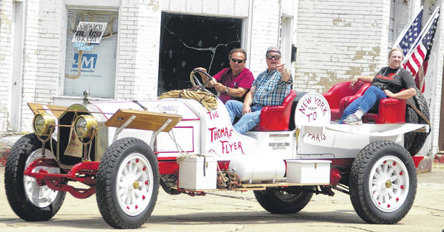 Rodney Rucker, left, of Winslow, Arizona, drives his replica 1907 Thomas Flyer through downtown Sidney on Tuesday afternoon. He was joined by Scott Dorsey, center, and Anna Remsberg, right, both of Sidney. The car replicates a vehicle that won a race from New York to Paris, which took 169 days to complete.