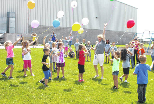 Christian Academy Schools kindergarten teacher Kendi Dray and her students release balloons on the final day of school Friday afternoon. The balloons included the name of the school and a picture of the school. The annual tradition signifies the kids' graduation from kindergarten.