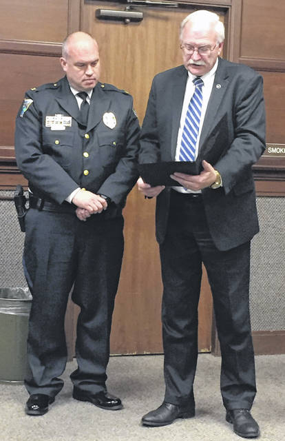 Police Chief Will Balling, lefts, receives a proclamation declaring May 15 as Peace Officers Memorial Day and Police Week as May 12-18, 2019, in the city of Sidney during Monday's Sidney City Council meeting.