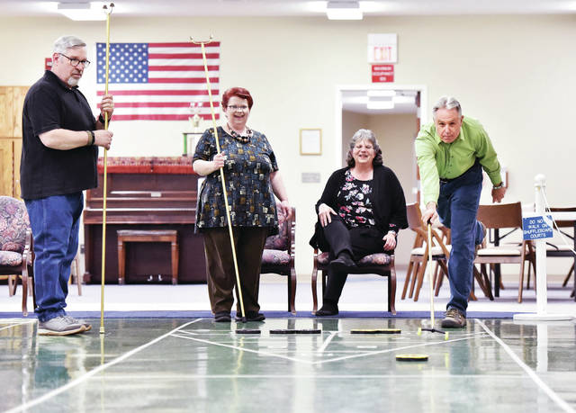Shuffleboarding at the Dorothy Love Amos Center on April 20 are, left to right, LeRoy and Lori Puterbaugh and Sandy and Peter Huelsebusch. LeRoy and Lori hope to join the team. They get some coaching from team member Peter as Sandy looks on.