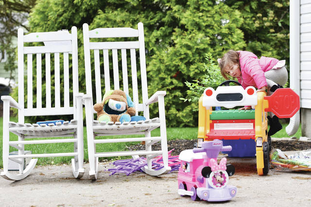 Ava Schlater, 2, of Botkins, daughter of Megan and Ryan Schlater, plays with one of her toys for perhaps the last time as her parents try to sell it and others during a garage sale Friday. The garage sale was at a home on North Main Avenue owned by Ava's grandparents Jeff and Deb Wagner.
