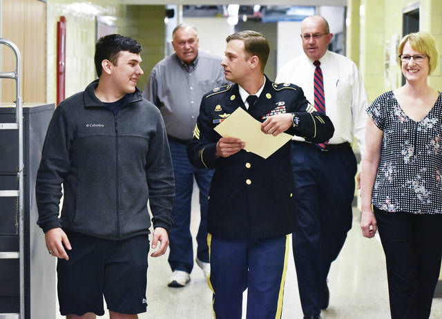 Derek Bertke, far left, 18, of Minster, walks with Army Sgt. Seth Coey, of Lima, who came to Minster High School to present Bertke with a certificate of enlistment in the US Army. Bertke will be going into the Engineering Corp.. Walking with them, left to right, are Bertke's grandpa Urban Bertke, of New Bremen, his father Dale Bertke and mother Karen Bertke, both of Minster. The presentation was held Thursday, May 9 during the Minster High School's annual student awards program.