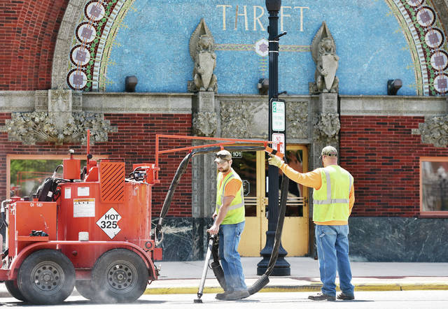 Derek Richard, left, of Sidney, dispenses crack seal on cracks which have formed in Court Street while Jeremy Martin, of Sidney, directs him Wednesday, May 15.