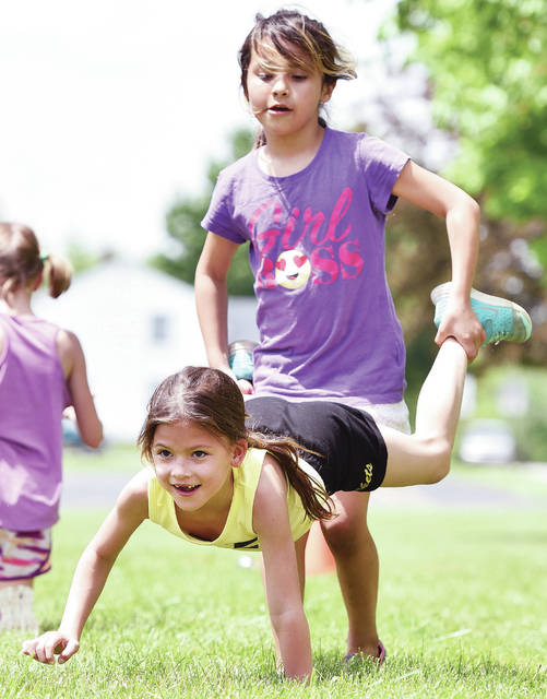 Raelyn Jones, front, 8, of Sidney, daughter of Brandon and Kristin Jones, and Aaliyah Cotterman, 9, of Piqua, daughter of Shayla and John Cogrove, take part in human wheelbarrow race during Whittier Elementary Field Day. The Field Day was held Thursday, May 16. Kids also had potato sack races, jumped in a jump house and ate Kona Ice from a truck parked in front.