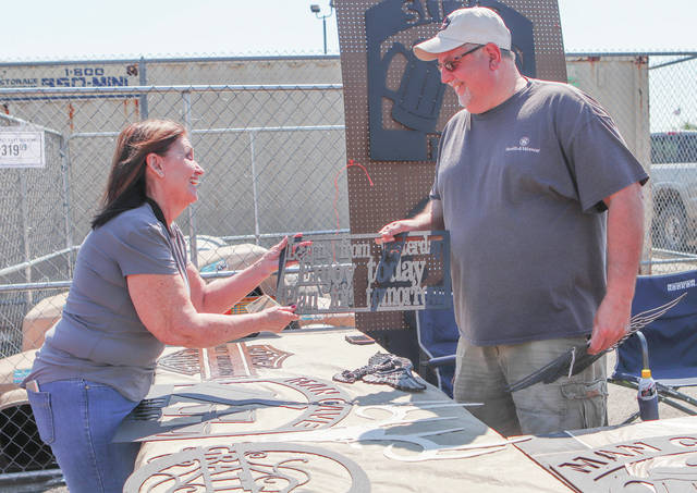 Susan Thompson, left, of Pleasant Hill buys some metal signs from Jeff Judy, of Jackson Center, who is the owner of JJ's Metal Art & Weld in Jackson Center. Judy was one of the vendors selling goods at the Sidney Tractor Supply community event Saturday, May 18.