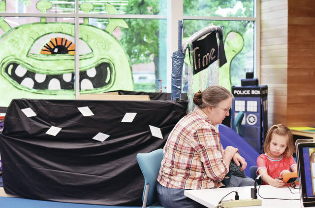 """A giant alien stares down at Trish Birt, left, of DeGraff, and her granddaughter, Kenzie Nessler, 4, of Huntsville, daughter of Logan and Karen Nessler, as they play educational games at the Amos Memorial Public Library Friday, May 24. The alien was painted on the window in preparation for the upcoming summer library program """"A Universe of Stories"""" which will run from May 28 to July 24. Different programs will cater to ages ranging from babies all the way to adults."""