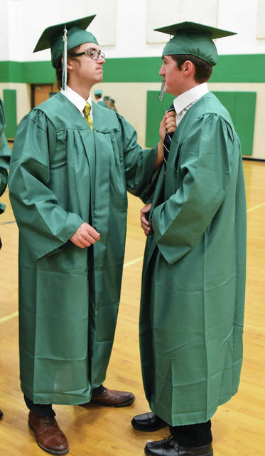 Preston Shannon, left, adjusts the tie of Austin Fry during the Anna High School graduation ceremony Sunday, May 26.