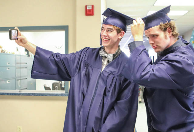 Christian Academy seniors Blake Lochard, left, of Russia, and Chuck Adkins, of Sidney, take a selfie before the start of their commencement ceremony Friday, May 24.