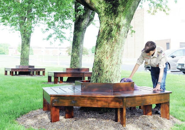 Boy Scout Troop 95 member TJ Leonard, 18, of Sidney, son of Bob and Kelly Leonard, dries the wraparound benches he installed in front of Sidney High School Saturday, May 25. Leonard made the handcrafted benches for his Eagle Scout project. Leonard had the Sidney High School band members in mind while building the benches because the band practices in front of the school and he wanted a place for them to sit down but the benches are for anyone who needs to sit.