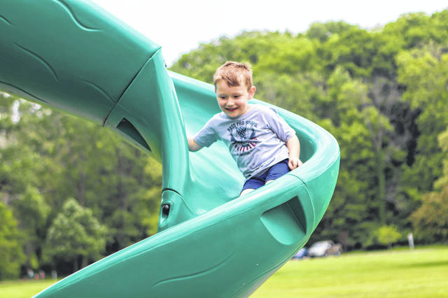 Wesley Slife, 5, son of April and Justin Slife, of Houston, goes down the slide while playing tag with some kids at the playground in Tawawa Park by the soccer fields.