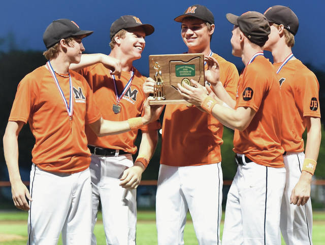 Minster players pose with the district champion trophy after beating New Bremen 11-2 on May 24 in Coldwater. The Wildcats beat Cincinnati Christian 1-0 in a Division IV regional final on Sunday in Coldwater to earn a state berth.