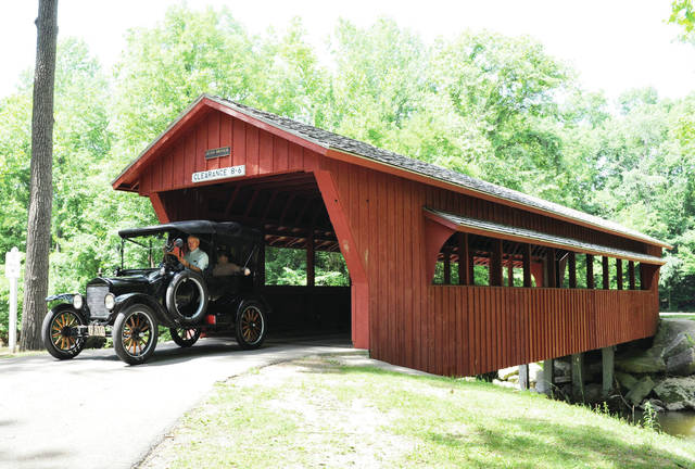 A Model T Ford driven by Gary Bertsch, of Anna, exits the covered bridge at Tawawa Park during the Tawawa Park Annual Cruise-In in honor of Anthony McLain, Saturday, June 29. Also in the car were Sandy Pence, of Anna, and her daughter Erin Pence, of Springfield. Around 250 cars took part in the car show which included free rides in Model T cars.