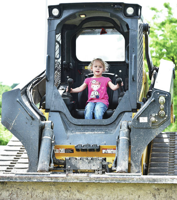 Stella Brumbaugh, 3, of Sidney, daughter of Lauren and Dwayne Prince, tries her hand at some construction equipment during Touch a Truck at Ferguson Construction Company Saturday, June 8.
