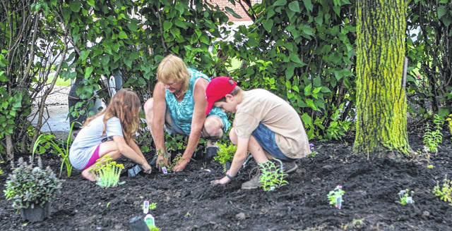 Denise McCune, of Fort Loramie, and her grandchildren Arabella Cassada, 7, and Austin Cassada, 11, plant flowers at Fair Haven Shelby County Home on Fair Road Monday, June 17. Arabella and Austin are the children of David Cassada, of Sidney, and Sara Gillott, of Miamisburg. Several volunteers worked to put down the landscaping supplies donated by Blue Acre Gardens, Sidney Landscaping, Lowe's, Walmart, Kris Elsner, Gehret Nursery, Roe Trucking, Bryce Refus and Kroger.