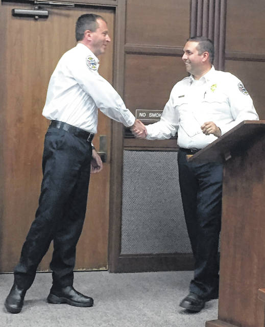 Newly promoted Fire Lieutenant Keith Wiley shakes Deputy Fire Chief Chad Hollinger's hand after he is introduced to Sidney City Council members during Monday's meeting. Wiley was recently promoted to lieutenant from a firefighter position. Hollinger was also introduced to council, by City Manager Mark Cundiff, as the new deputy fire chief Monday. Hollinger was recently promoted from an assistant chief position. Newly promoted Assistant Fire Chief Dallas Davis, who was recently promoted from a lieutenant position, was also being introduced when he was called away for a fire or EMS call.