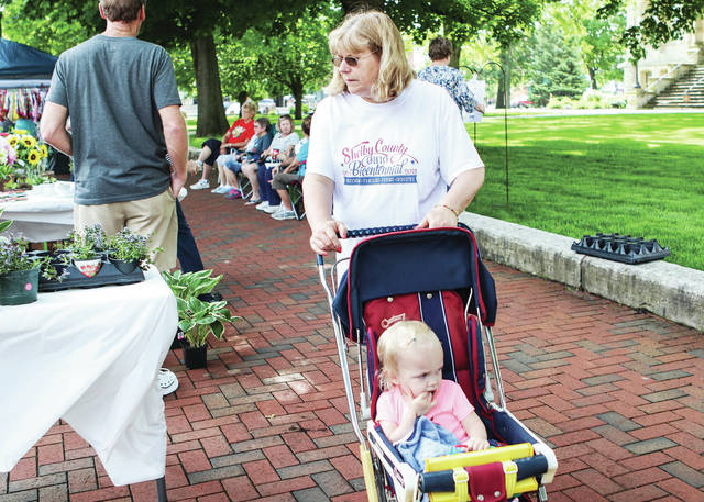 Tilda Phlipot, and her granddaughter Madelyn Macke, 2, both of Sidney, walk through The Great Sidney Farmers Market Saturday, May 25. Madelyn is the daughter of Chris and Sarah Macke.