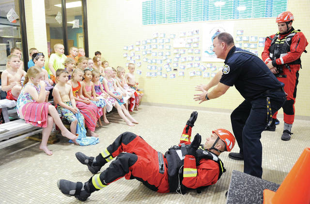 Showing a group of Sidney-Shelby County YMCA water safety students what to do if they are ever swept away in fast moving water are Sidney Fire Assistant Chief Dallas Davis, left to right, Fire Lt. Jason Truesdale and Firefighter Collin Habel. The firefighters spent the day Thursday, June 6, teaching the groups age K-sixth grade, about water safety.
