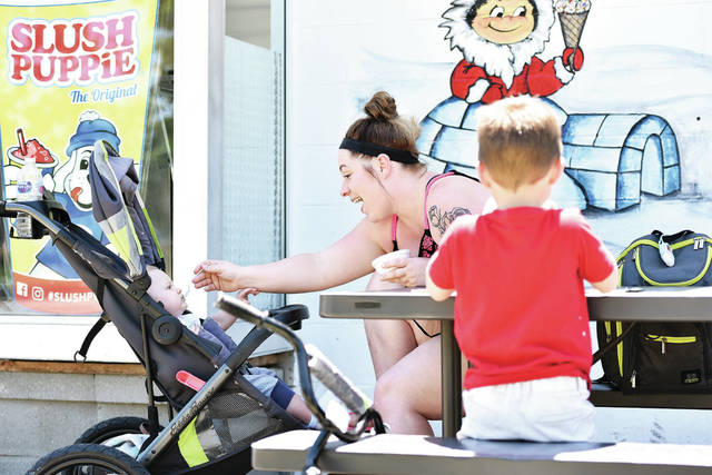 Paige Little, center, feeds ice cream to her son Kane Kearns, 8 months, son of Joshua Kearns, at Chilly Jilly's Wednesday, June 12. Sitting with Little was her other son, Carter Morrison, 6, all of Sidney, son of Alex Morrison. A sunny sky and temperatures in the upper 70s made for good ice cream-eating weather.