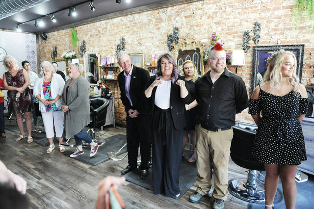 The Royal Parlour owner Allison Marlow, center, gives a talk during a ribbon cutting for her new salon Friday. Standing next to her are President of the Sidney-Shelby County Chamber of Commerce Jeff Raible, left, and her husband Kyle Marlow, right. The Royal Parlour is located at 107 N. Ohio Ave. in Sidney.