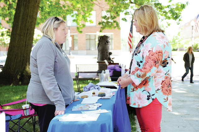 Wilson Health representative social worker Hallie Hurley, left, of Anna, talks with Catholic Social Services social worker Dianne Pleiman, of Fort Loramie, during Elder Abuse Awareness Day on the courtsquare Friday, June 14. Free hotdogs were given away.